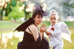 Moter med sonen som spelar ängel, och demonen Royaltyfria Bilder