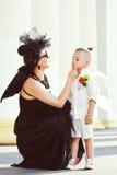Moter med sonen som spelar ängel, och demonen Royaltyfri Foto