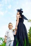 Moter med sonen som spelar ängel, och demonen Arkivfoto