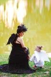 Moter med sonen som spelar ängel, och demonen Royaltyfri Bild