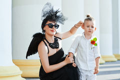 Moter med sonen som spelar ängel, och demonen Fotografering för Bildbyråer