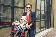 Moter och behandla som ett barn dottern på en cykel Royaltyfri Foto