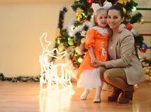 Moter och dotter nära julträdet Arkivfoton