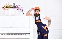 Moteur barbu beau posant à côté du rétro piano d'isolement sur le fond blanc Petite coupure de travail fatiguant Photographie stock