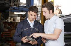Moteur de difficulté de Helping Apprentice To de mécanicien images stock
