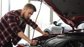Moteur de examen de cutomer masculin beau d'une voiture à la salle d'exposition de concessionnaire clips vidéos