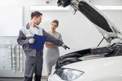 Moteur de voiture de explication de jeune dépanneur masculin au client féminin dans l'atelier de réparations d'automobile Image libre de droits
