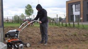 Moteur faible de début d'homme de cultivateur et travailler dur dans la cour de maison urbaine clips vidéos