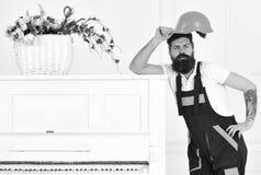 Moteur fatigué appréciant la petite coupure du travail d'isolement sur le fond blanc Travailleur barbu enlevant son casque de pro Photographie stock libre de droits