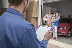 Moteur tenant le presse-papiers et la facture, famille à l'arrière-plan photos libres de droits