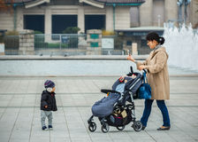 Mothe and Child in Ueno Park. TOKYO, JAPAN - NOVEMBER 25: Ueno Park in Tokyo, Japan on November 25, 2013. Unidentified Japanese mother use a smartphone takes Stock Photos