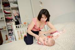 Fostra och dottern på säng royaltyfri foto