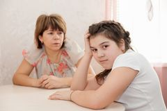 Mother abusing at teenager`s daughter. Furious mother scolding schoolgirl daughter stock photo