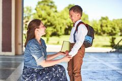 Mother accompanies the child to school. mom encourages student accompanying him to school. a caring mother looks tenderly at her royalty free stock image
