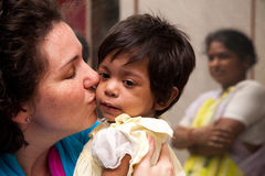 Mother and adopted child. Mother's first time seeing adopted child. Color image and mother is kissing child with orphanage worker in background Royalty Free Stock Photography