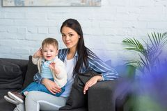 Mother with adorable baby boy on hands sitting on sofa. At home royalty free stock photo