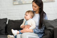 Mother with adorable baby boy on hands sitting on sofa. At home stock photos
