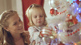Mother with adorable baby decorate a Christmas tree at home Stock Photo