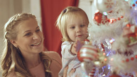 Mother with adorable baby decorate a Christmas tree at home Royalty Free Stock Photography
