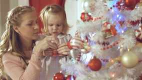 Mother with adorable baby decorate a Christmas tree at home Stock Image