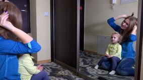 Mother with adorable girl pose in front of mirror stock footage