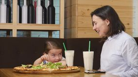 Mother and adorable little girl having breakfast in a cafe.  stock video footage