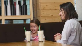 Mother and adorable little girl having breakfast in a cafe.  stock footage