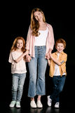 Mother with adorable redhead children standing together and holding hands isolated on black Stock Images