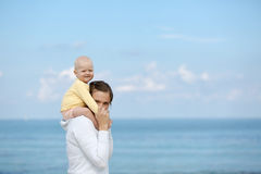 Mother and adorable smiling baby cuddling. Devoted mother and adorable smiling child cuddling, spending bonding quality time on beach with blue waters in the Royalty Free Stock Image