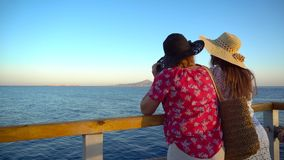 Mother and adult daughter admiring sea landscape and having fun on pier. View of Tiran island in Egypt. Summer vacation. 4k stock video footage