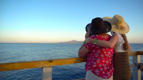 Mother and adult daughter admiring sea landscape and talking on pier. View of Tiran island in Egypt. Summer vacation. 4k stock video footage