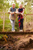 Mother and adult daughter on a bridge in a forest, to camera stock photography
