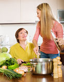 Mother and adult daughter cooking at  kitchen Stock Photos