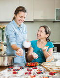 Mother with adult daughter  making berries dumplings Royalty Free Stock Photography