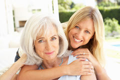 Mother And Adult Daughter Relaxing On Sofa Stock Photography