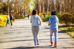 Mother and adult daughter running for sport in park for better fitness. royalty free stock photo