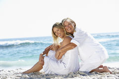 Mother And Adult Daughter Sitting Together On Beach Stock Photo