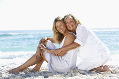 Mother And Adult Daughter Sitting Together On Beach Stock Images