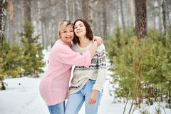 Mother and adult daughter walking in winter forest snowfall royalty free stock photo