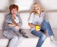 Mother with adult daughter watching television Stock Photography
