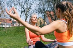 Mother and adult daughter in yoga mediation outdoors Royalty Free Stock Images