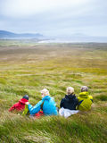 Mother with adult daughters resting on meadow during walk Stock Photography