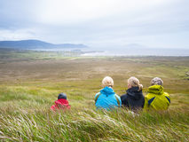 Mother with adult daughters resting on meadow during walk. A women with her adult daughters is taking a rest during a walk on Achill Island, Ireland Stock Photos