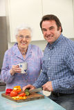 Mother and adult son preparing meal together Royalty Free Stock Photos