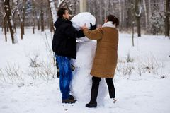Mother and adult son sculpt a big real snowman. Happy family in winter park Royalty Free Stock Photography