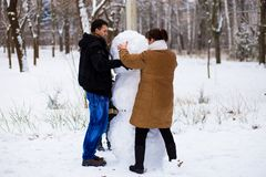 Mother and adult son sculpt a big real snowman. Happy family in winter park Stock Photography