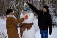 Mother and adult son sculpt a big real snowman. Happy family in winter park Royalty Free Stock Photo