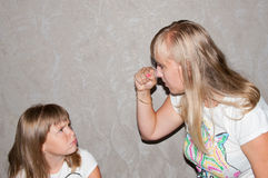 Mother against daughter. Mom swings at his daughter with his fist, hurting child Royalty Free Stock Photography