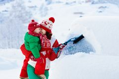 Free Mother And Child Brushing Off Car In Winter. Stock Photo - 130015590