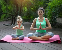 Mother And Daughter Doing Exercise Practicing Yoga Outdoors Stock Images